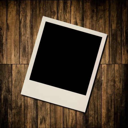 Blank instant photo frame on old wooden background photo