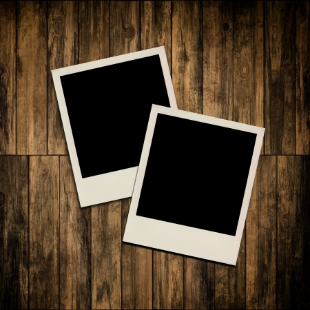 Blank instant photo frames on old wooden background photo