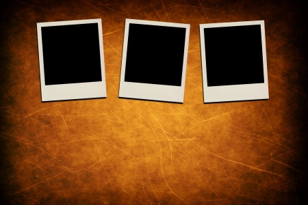 Blank instant photo frames on grunge brown background