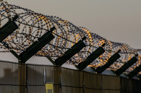 Military fence with a barbed wire photo