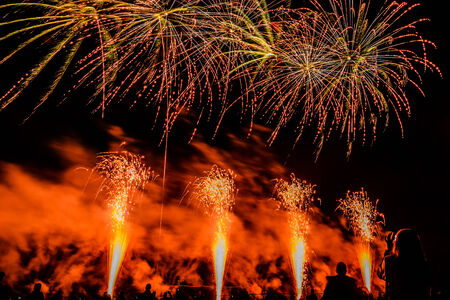 spectator: Colorful fireworks of various colors over night sky with spectators