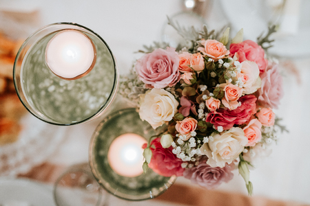 Colorful flower wedding center-piece decoration with pink and white roses and tow candles from top view