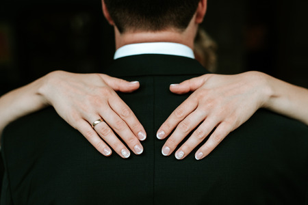 Bride hands with rings on the back of the groom in black tuxedo