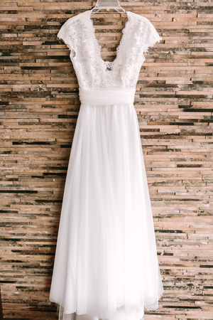 Elegant white wedding dress hanging on modern bricked wall Stock fotó