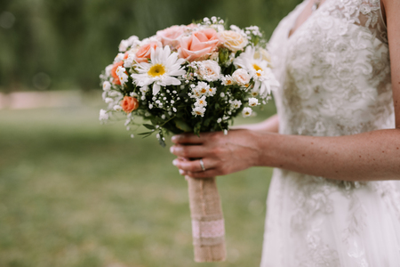 Bride holding the wedding bouquet with pink and white flowers on white wedding dress