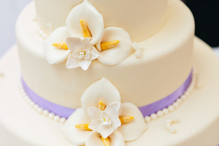 Marzipan flowers and purple ribbon on wedding cake with white flower decoration Archivio Fotografico