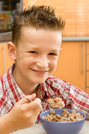 comiendo cereal: Ni�o sonriente, comiendo un taz�n de cereales