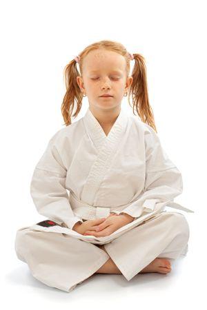 kimono: Little girl meditation on karate school, isolated on white