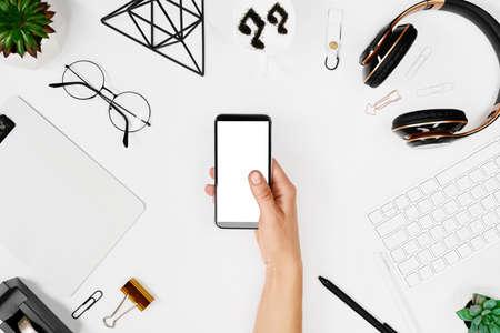 Man using phone over creative workspace mockup