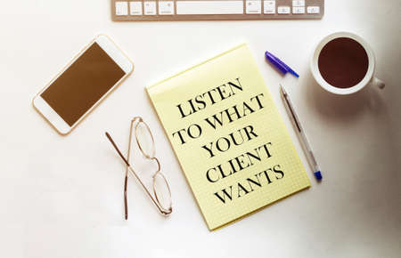 LISTEN TO WHAT YOUR CLIENT WANTS text on the yellow paper with phone, coffee, pen Banque d'images