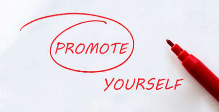 white paper with text PROMOTE YOURSELF on the white with red marker