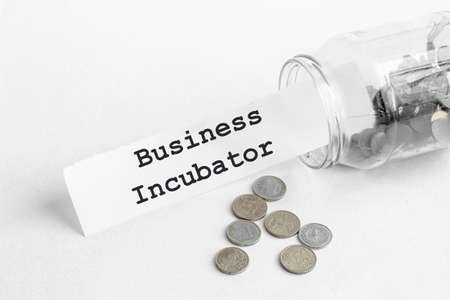 sticking out of a jar of coins a piece of paper with a text Business Incubator