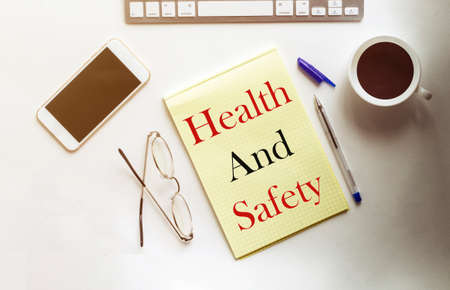 Health And Safety text on the yellow paper with phone, coffee, pen