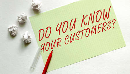 yellow paper with text Your Customers on the white with red marker Фото со стока