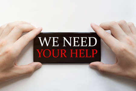 male hands are holding black phone with text We Need Your Help on white background