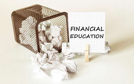 white lumps of paper fall out of the case to the paper in the inscription FINANCIAL EDUCATION