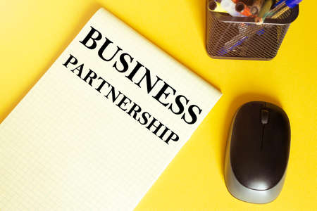 computer mouse, pens, felt-tip pens, notepad with text BUSINESS PARTNERSHIP on a yellow background