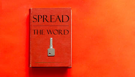 red book with text SPREAD THE WORD and a key on a red background