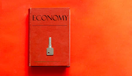 red book with text Economy and a key on a red background