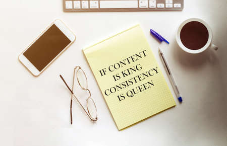 If Content Is King Consistency Is Queen text on the yellow paper with phone, coffee, pen Banque d'images