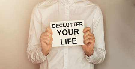 man take a paper with text Declutter Your Life on the shirt with office background