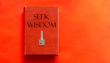 red book with text Seek Wisdom and a key on a red background