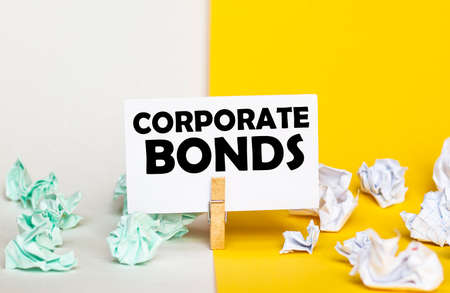 white paper with text Corporate Bonds on a clothespin on yellow and white backgrounds with paper wads of different colors