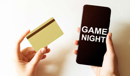 gold card and phone with text disaster recover plan Game Night in the female hands