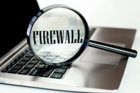 Laptop computer with magnifying glass, concept of search. Firewall