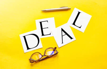white paper with text DEAL on a yellow background with glasses and pen