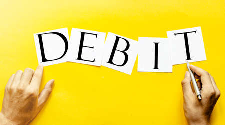 white paper with text DEBIT on a yellow background with man's hands Foto de archivo