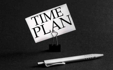 white paper with text Time Plan on a black background with stationery