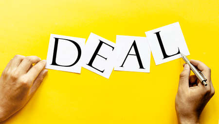 white paper with text DEAL on a yellow background with man's hands