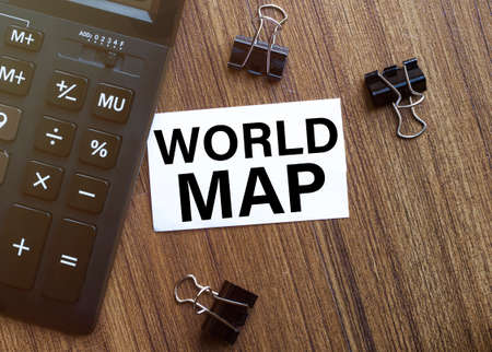 white paper with text World Map on a black background with stationery Foto de archivo