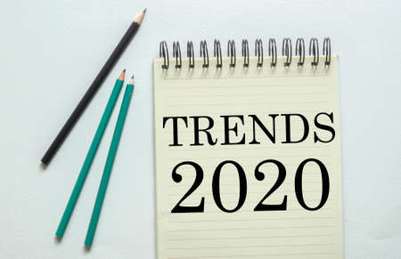 two green one black pencil with text Trends 2020 in the notebook on the white background