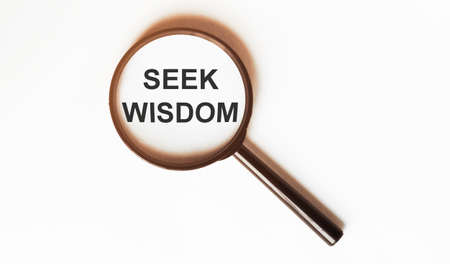 Seek Wisdom on a sheet under a magnifying glass