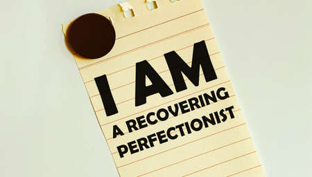 yellow paper with text I Am A Recovering Perfectionist on the white fridge Foto de archivo