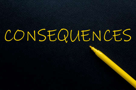 Consequences Yellow Pen with yellow text own rent at the black background 免版税图像