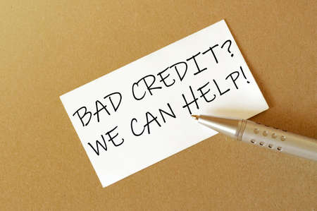 pen, white paper with text Bad Credit We Can Help on the brown background 免版税图像