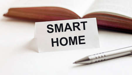 piece of paper with text Smart Home on the background of books, pens, on a white background