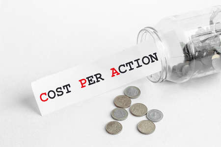 sticking out of a jar of coins a piece of paper with a text Cpa Cost Per Action on a white background
