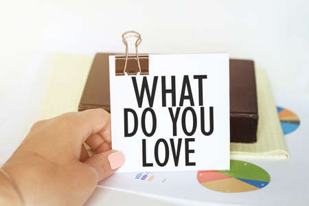 woman s hand holds a piece of paper with text What Do You Love on the background of graphs and notepad Imagens