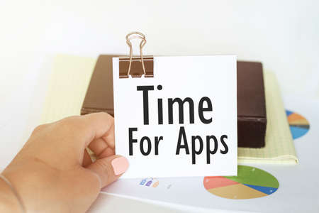 woman s hand holds a piece of paper with text Time For Apps on the background of graphs and notepad