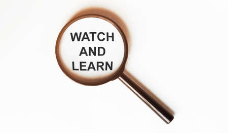 Watch And Learn on a sheet under a magnifying glass