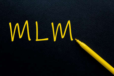 MLM Multi Level Marketing Yellow Pen with yellow text own rent at the black background