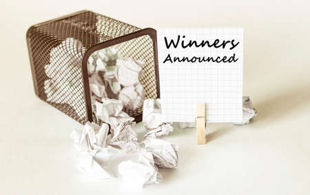 white lumps of paper fall out of the case to the paper in the inscription Winners Announced 写真素材