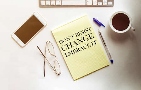 Do Not Resist Change Embrace It text on the yellow paper with phone, coffee, pen Banque d'images