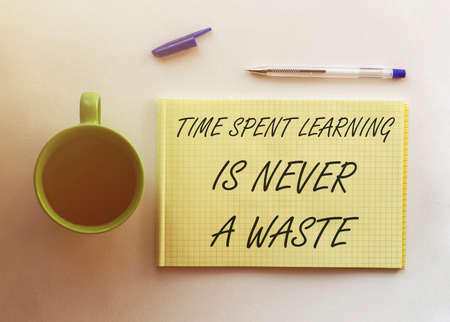 man take a paper with text Time Spent Learning Is Never A Waste on the shirt with office background