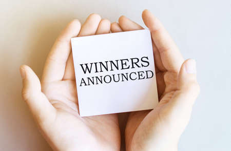 white paper with text Winners Announced in male hands on a white background