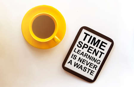 coffee and tablet with text Time Spent Learning Is Never A Waste on the white background